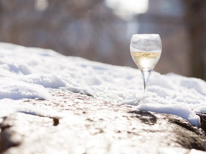 Surface level view of a glass of white wine in snow